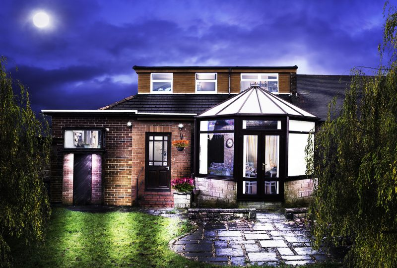 Semi-detached house photographed in a fine art style with pools of light and detail inside the conservatory